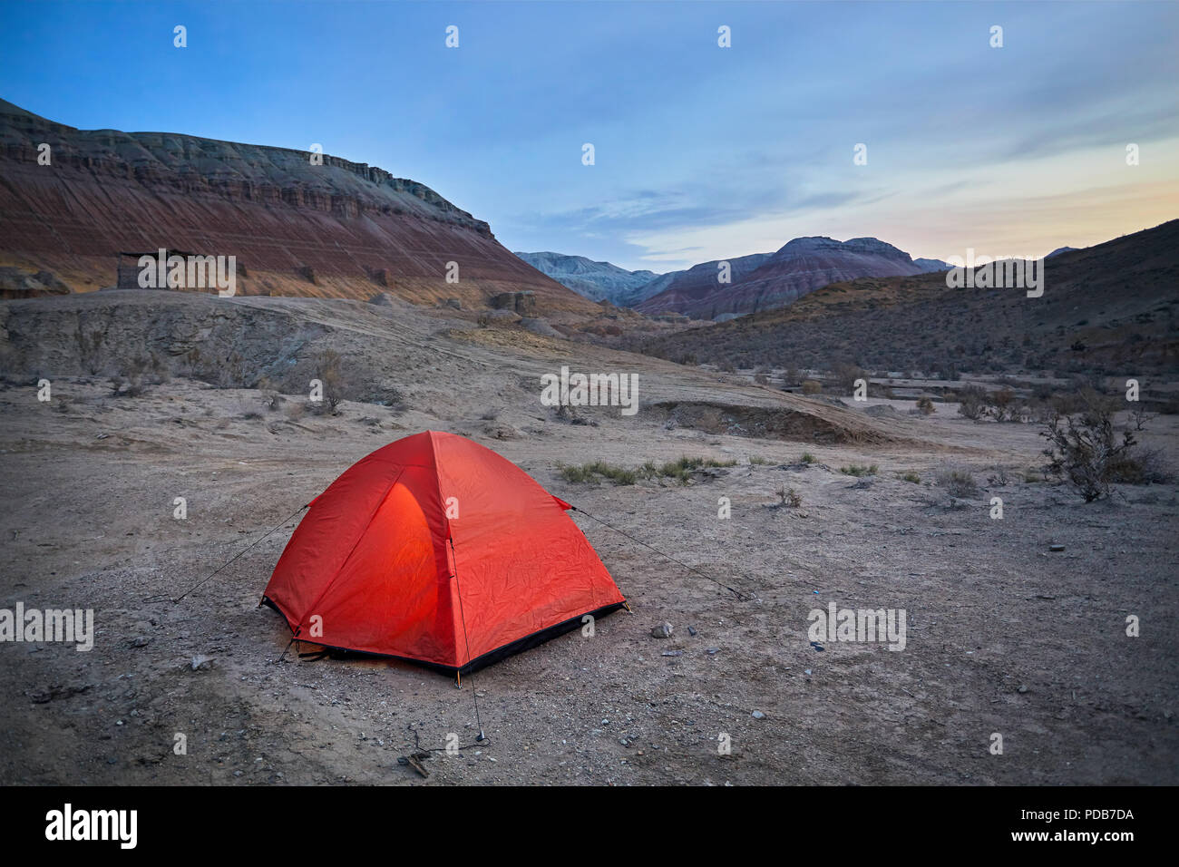 Touristic orange tent in the Desert mountains at sunrise in Kazakhstan Stock Photo