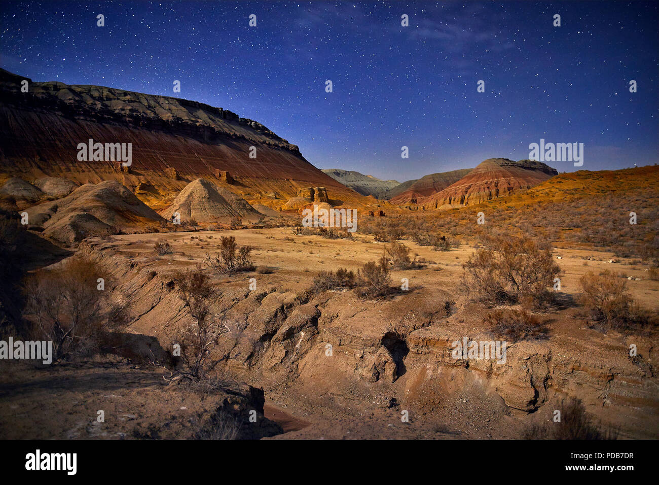 Red mountains in the canyon desert at night starry sky background. Astronomy photography of space and landscape. - Stock Image
