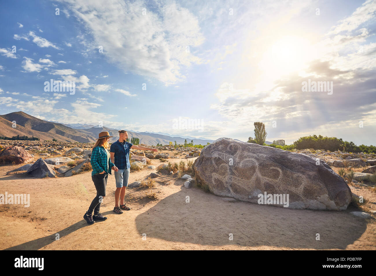 Couple in blue checkered shirt in the open air museum near stone with ancient petroglyph of goats at Kyrgyzstan. Culture Heritage Museum. - Stock Image