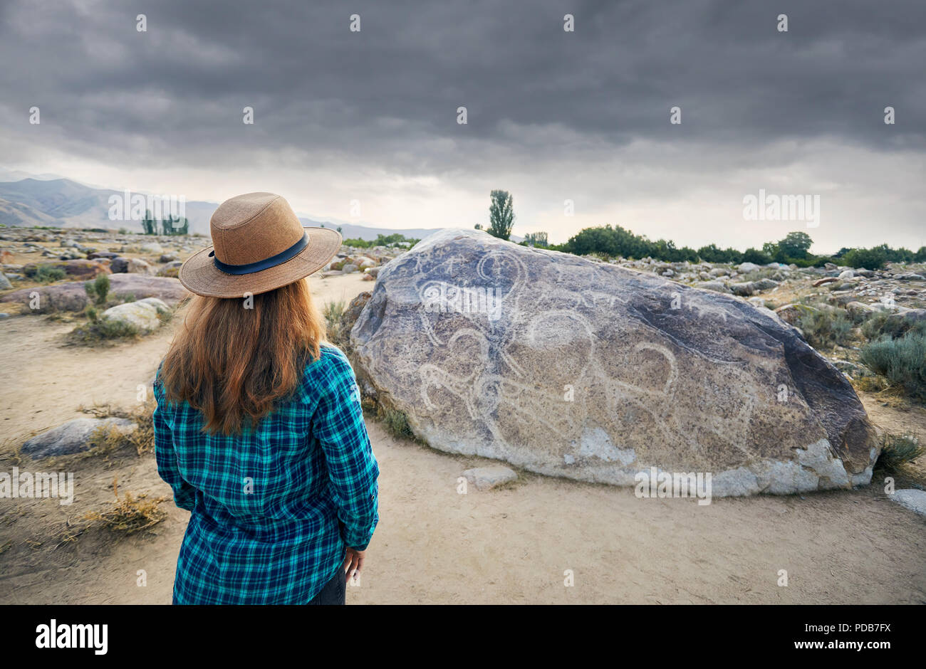 Woman in Hat in blue shirt in the open air museum near stone with ancient petroglyph of goats at Kyrgyzstan. Culture Heritage Museum. - Stock Image