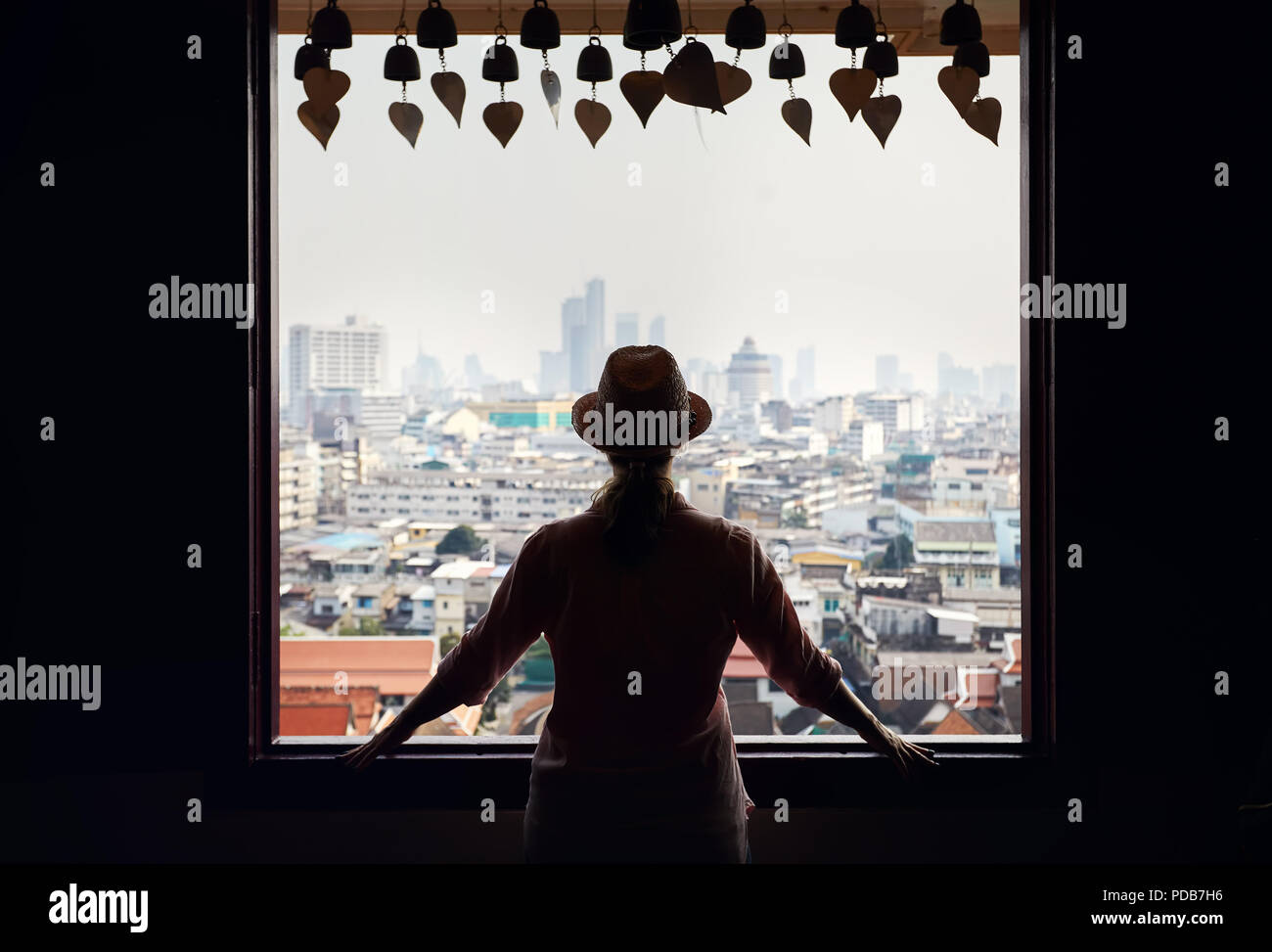 Silhouette of tourist woman looking in window to Bangkok city view of skyscrapers business district from Golden Mountain Pagoda Wat Saket at overcast  Stock Photo