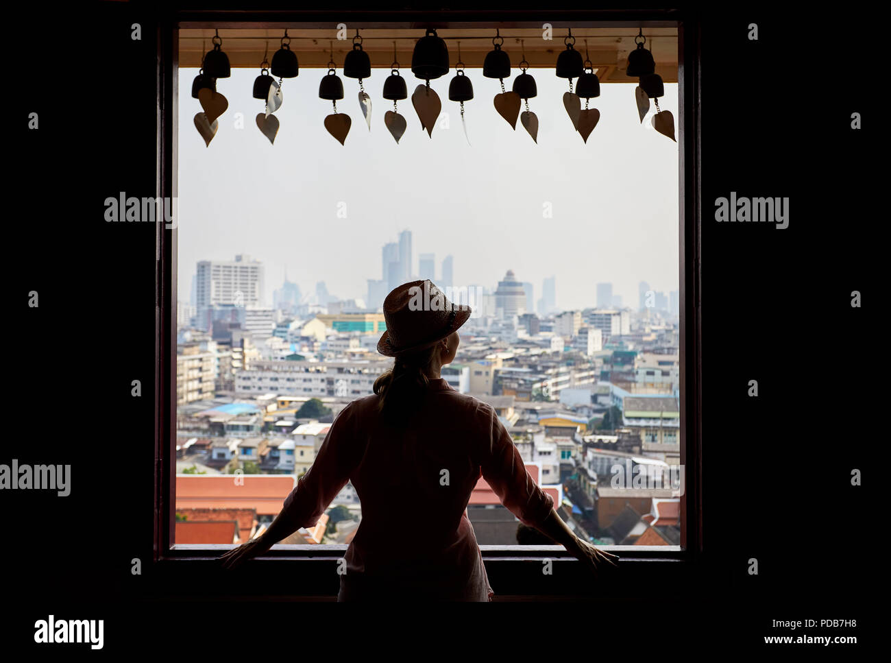Silhouette of tourist woman looking in window to Bangkok city view of skyscrapers business district from Golden Mountain Pagoda Wat Saket at overcast  - Stock Image