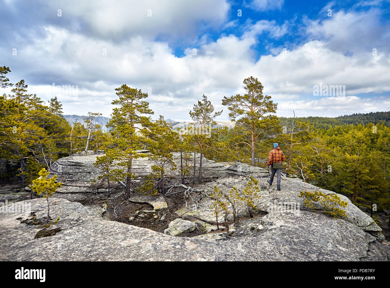 Man in brown jacket walking to the beautiful forest in Karkaraly national park in Karkaralinsk, Central Kazakhstan - Stock Image