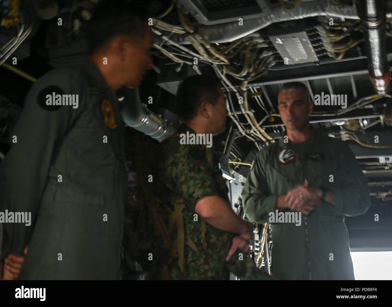 Lieutenant Col. Joshua M. Smith, commanding officer of Marine Medium Tiltrotor Training Squadron-204 with 2nd Marine Aircraft Wing, goes over the schematics of the MV-22 Osprey with Maj. Gen. Yoshiki Adachi, Defense and Military Attaché, Embassy of Japan, on Marine Corps Air Station New River, N.C., Aug. 2, 2018. Adachi is visiting the Marines and Sailors of II Marine Expeditionary Force to continue to build relationships and understand II MEF's mission and activities in the western hemisphere in regards to its amphibious capabilities and operations. (U.S. Marine Corps photo by Lance Cpl. Samu - Stock Image