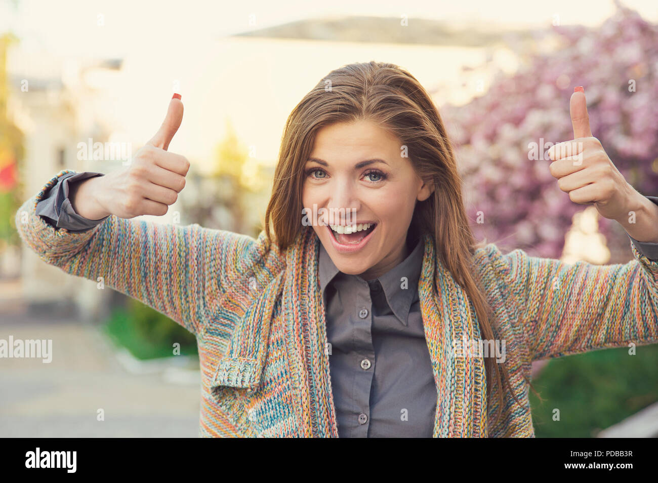 Bright young woman looking super excited while holding thumbs up in approval and smiling at camera outdoors - Stock Image