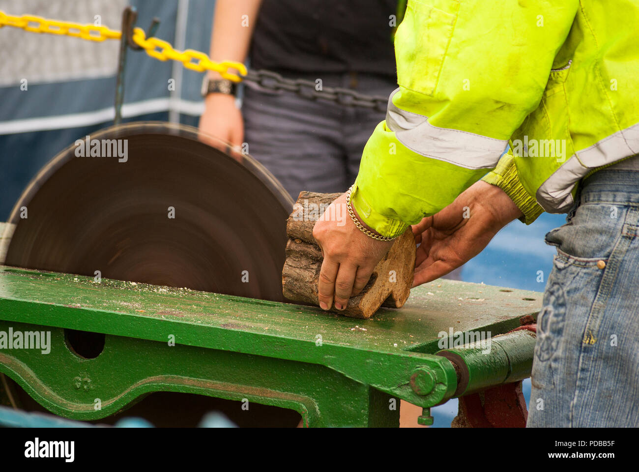 A man cutting wood on a table saw with fingers very close to the spinning blade - Stock Image