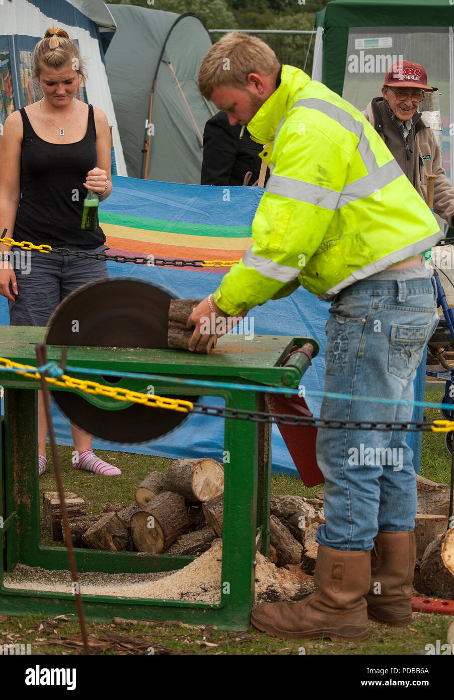 A man using a table saw with no personal protection. - Stock Image