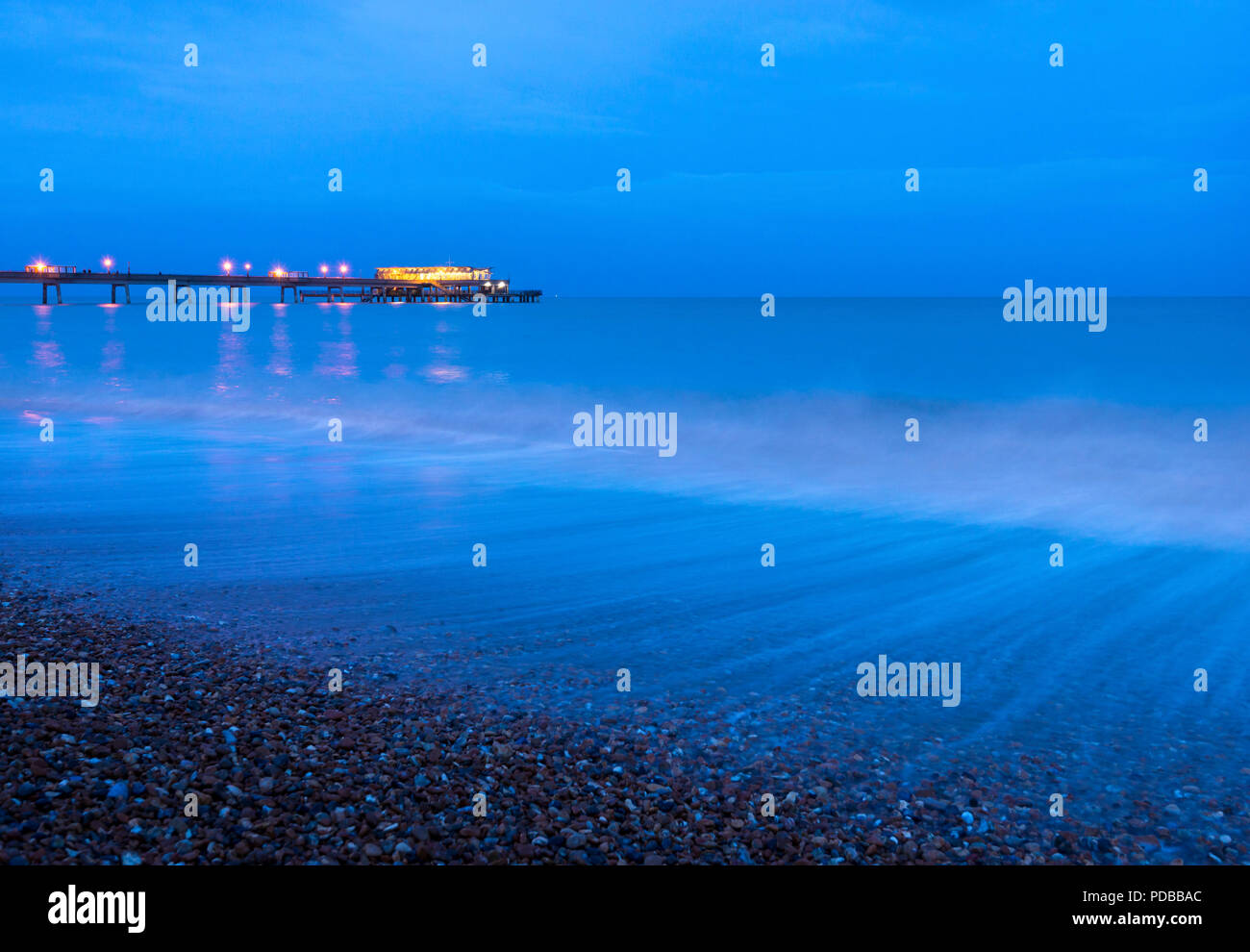 Waves crashing along Deal seafront at dusk with Deal Pier illuminated in the background. - Stock Image