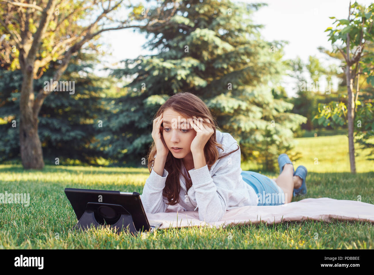 Portrait of young white Caucasian woman lying in park on grass watching digital tablet. Girl student worried feeling stressed. Strong emotion, funny f - Stock Image