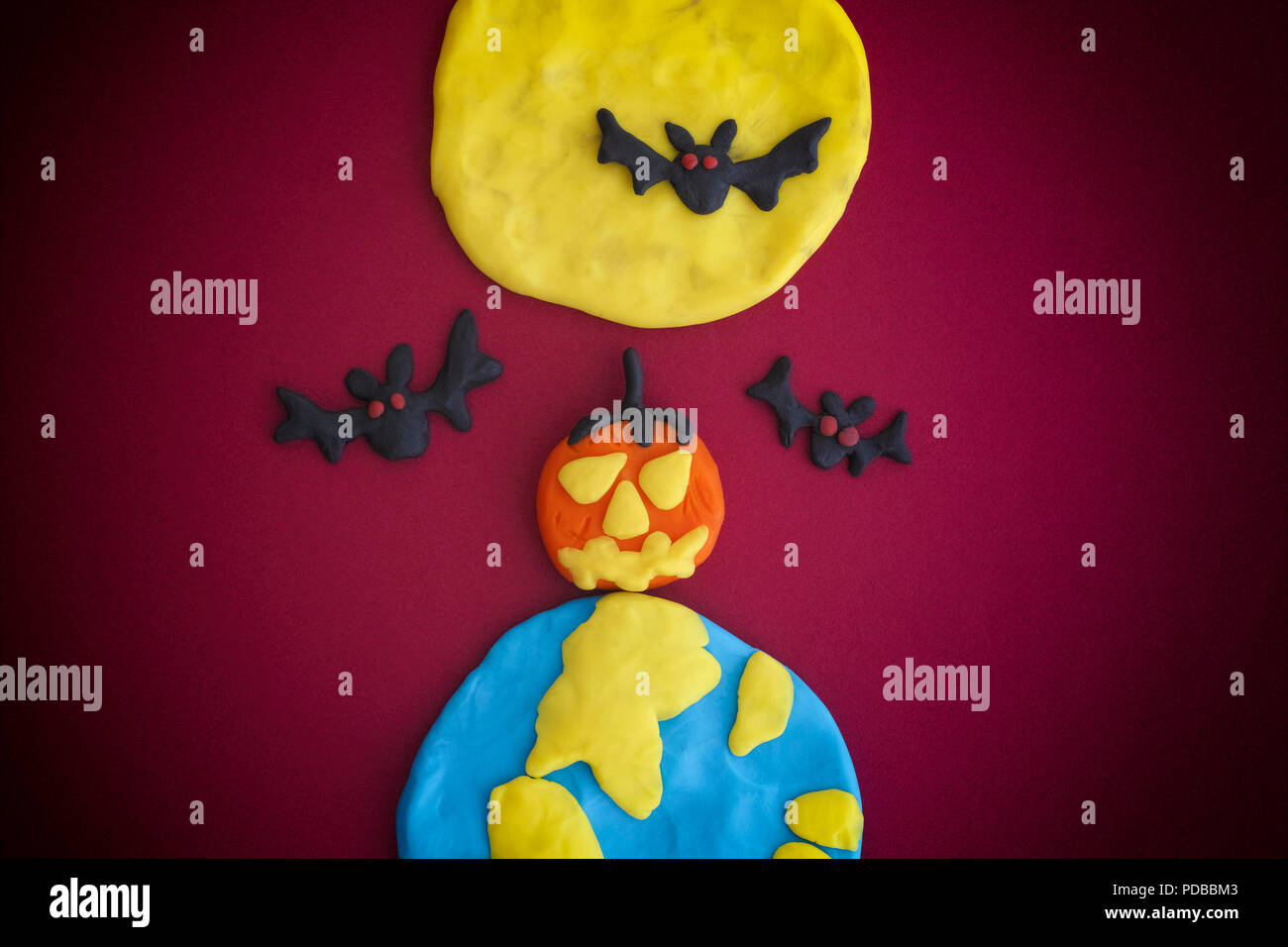 Happy Halloween. The Moon, Earth, pumpkin and bats are made out of modeling clay. - Stock Image