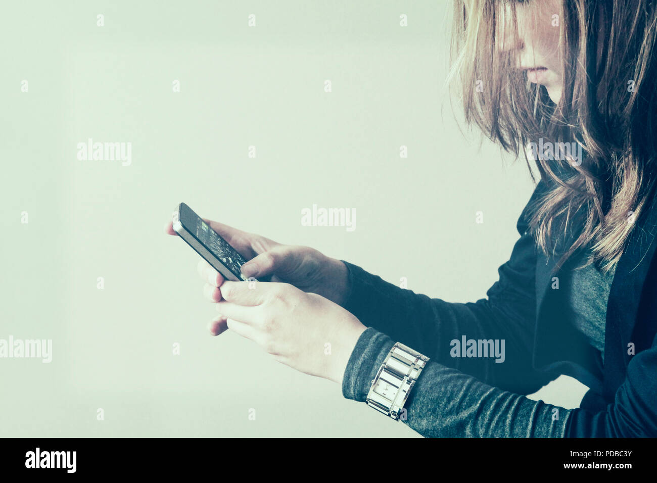 Pretty young womanl looking at phone with apps - Stock Image