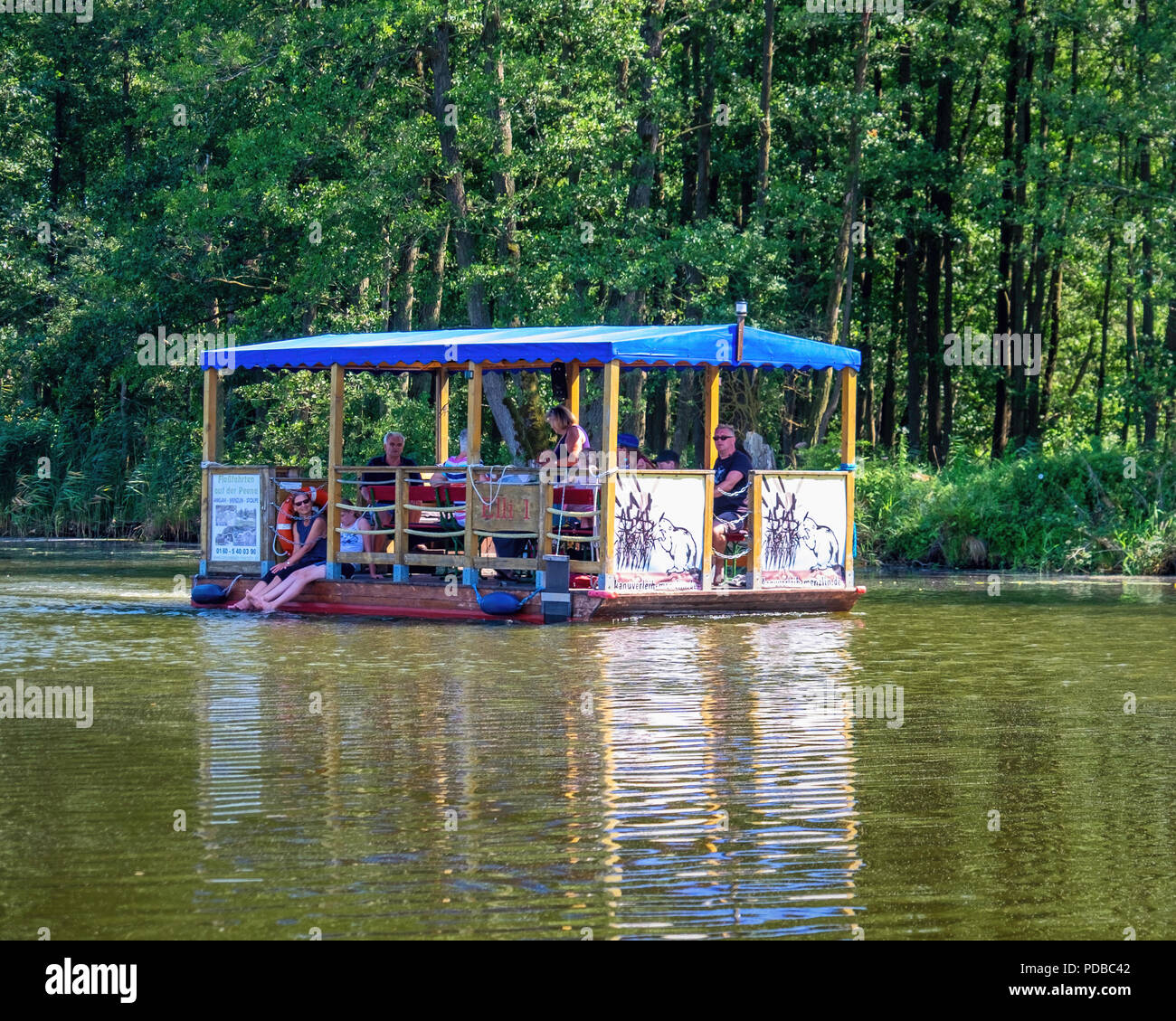 Germany, River Peene - Tourists cruise on pleaure boat on unspoilt river in Peenetal nature conservation park - Stock Image