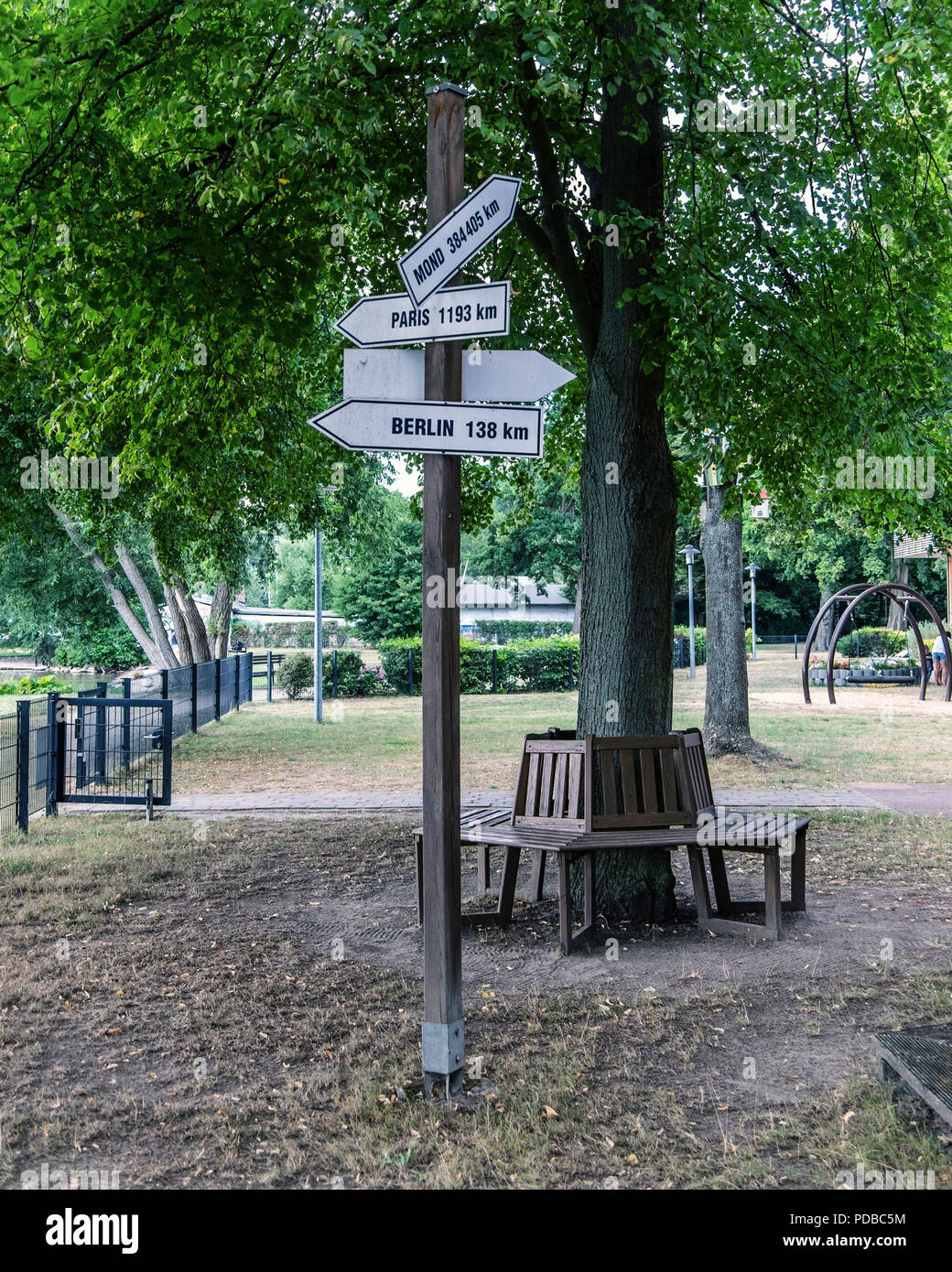 Funny sign with distances to Paris Berlin & the moon at Tollensee lake, Neubrandeburg,Mecklenburg Lake District,Germany - Stock Image