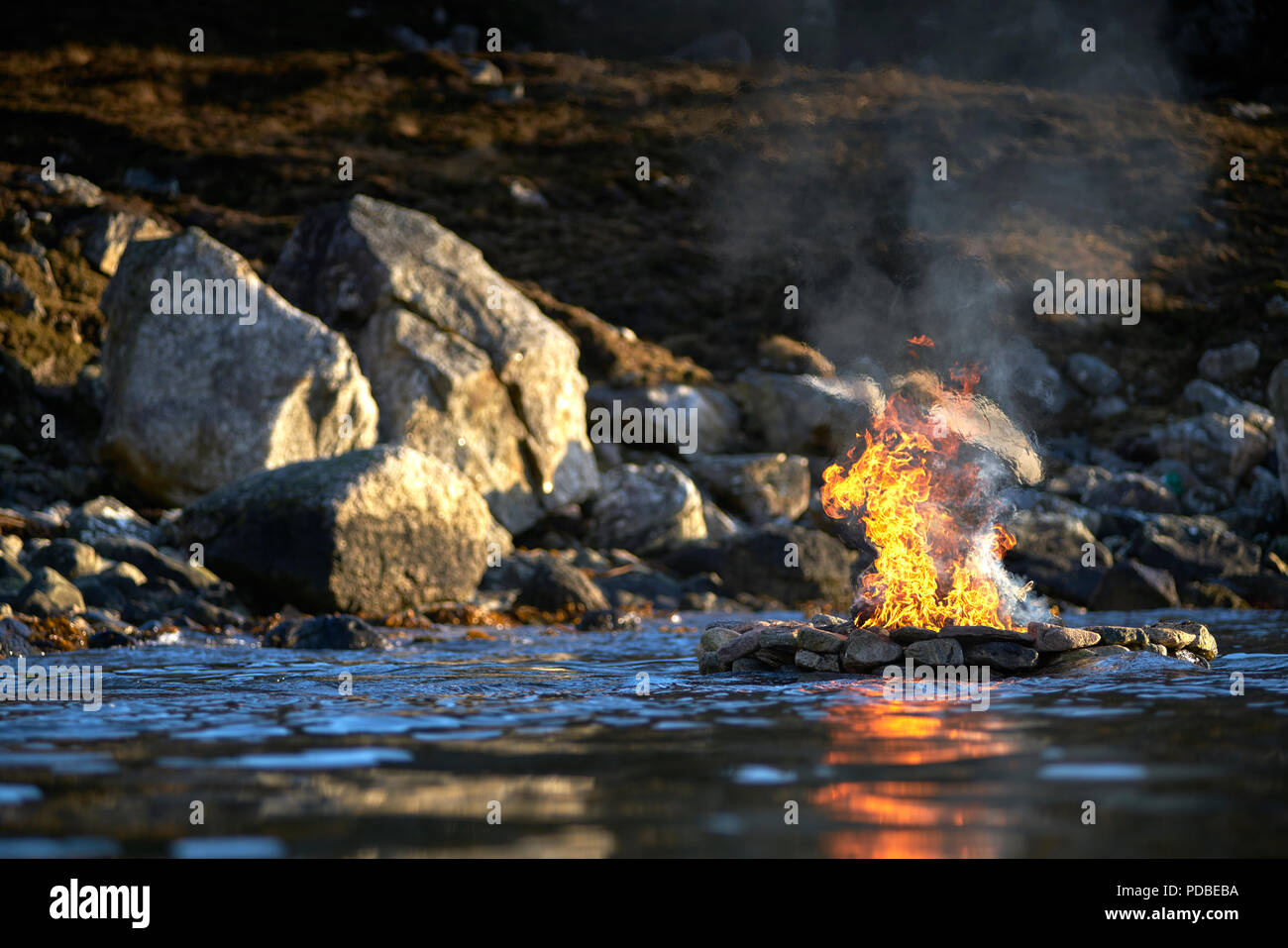 Firestack by Artist Julie Brook.West coast of The Isle of Lewis. Scotland. Elemental sculpture of hollow stone cairn with fire lit on an incoming tide - Stock Image