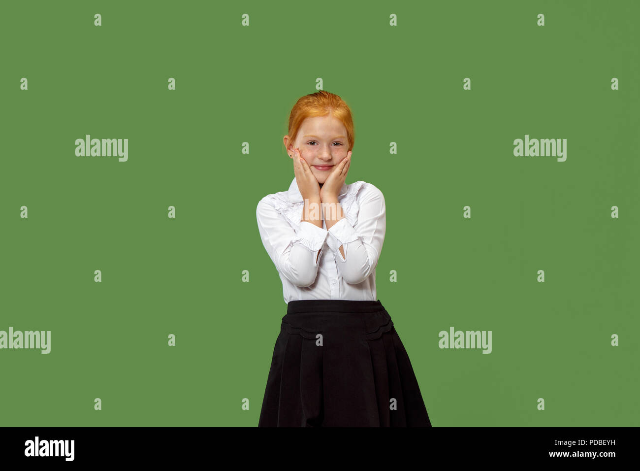 Happy teen girl standing, smiling isolated on trendy green studio background. Beautiful female half-length portrait. Human emotions, facial expression concept. - Stock Image