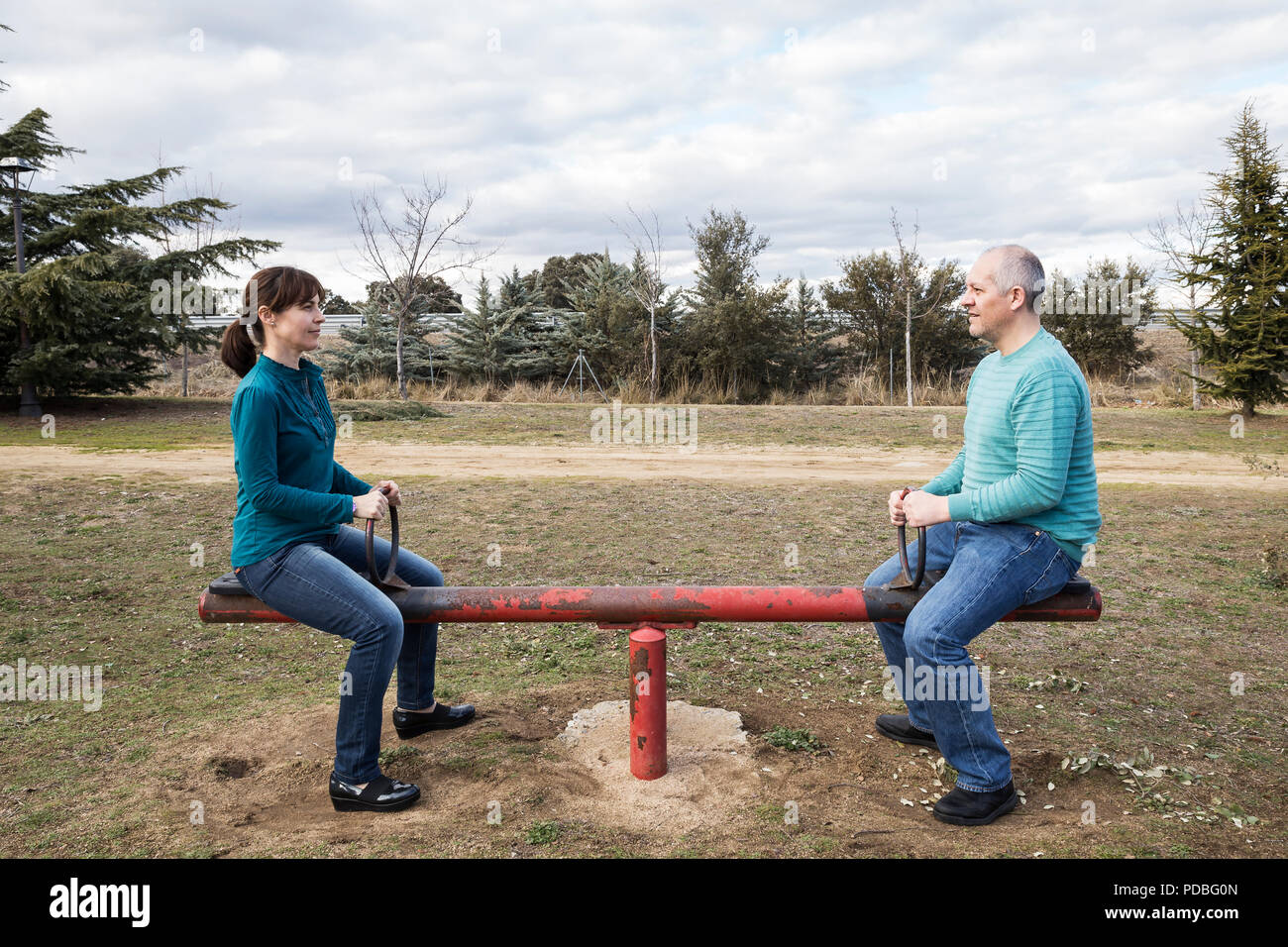 woman and man mounted on a seesaw representing gender equality - Stock Image
