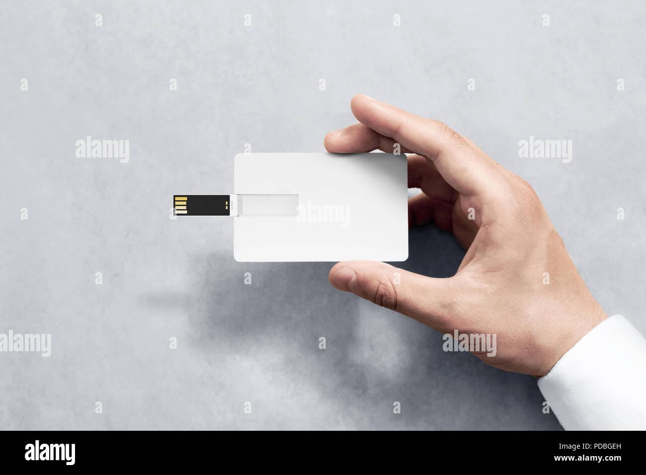 Blank white plastic wafer usb card design mockup holding hand. Visiting flash drive namecard mock up. Call-card disk souvenir presentation. Flat credit stick adapter. Bussiness favor in mans arm - Stock Image
