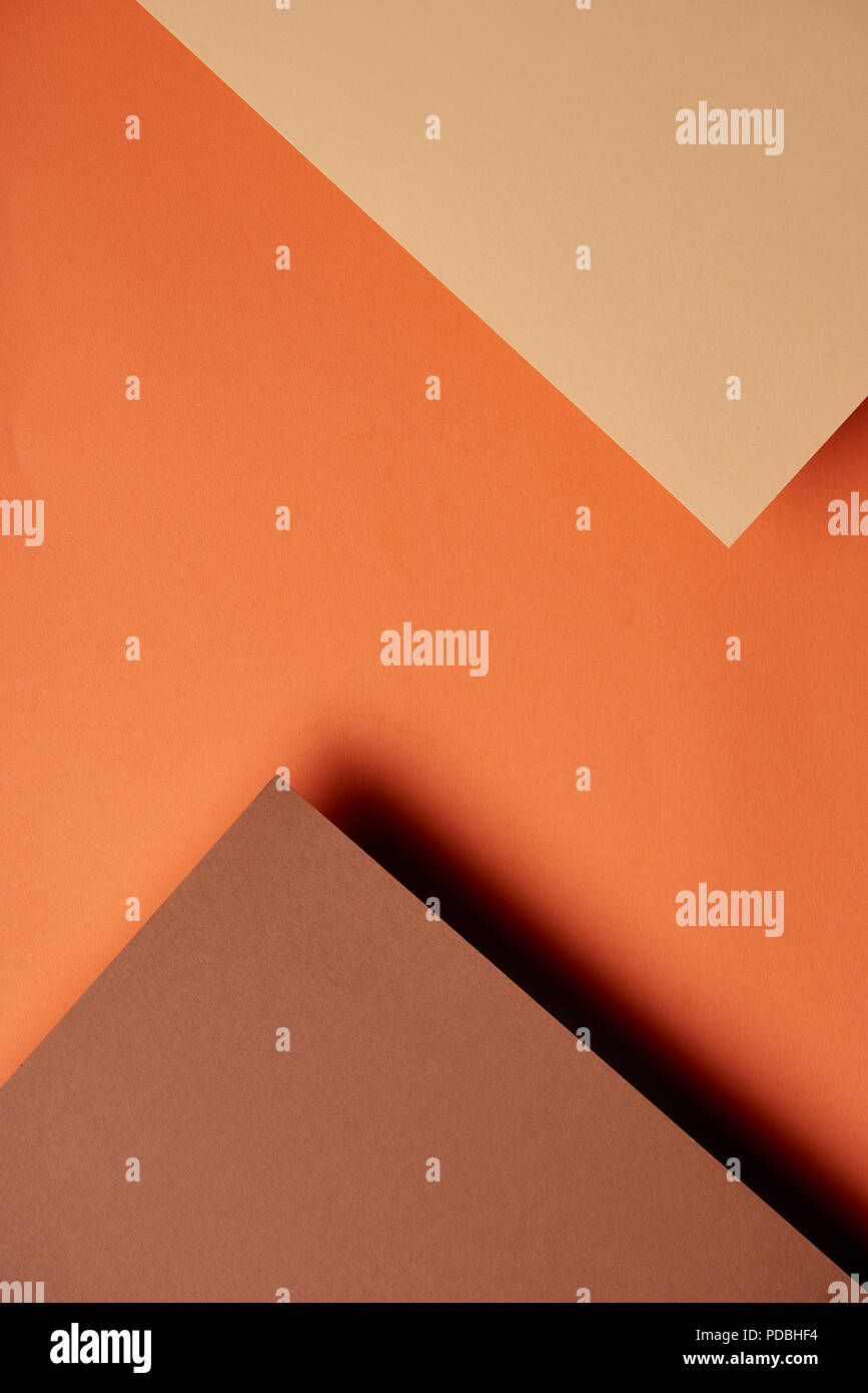 Paper sheets in brown and orange tones background - Stock Image