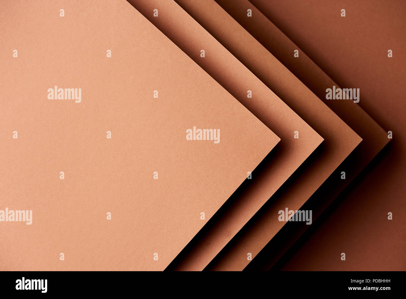 Paper sheets in brown tones background - Stock Image