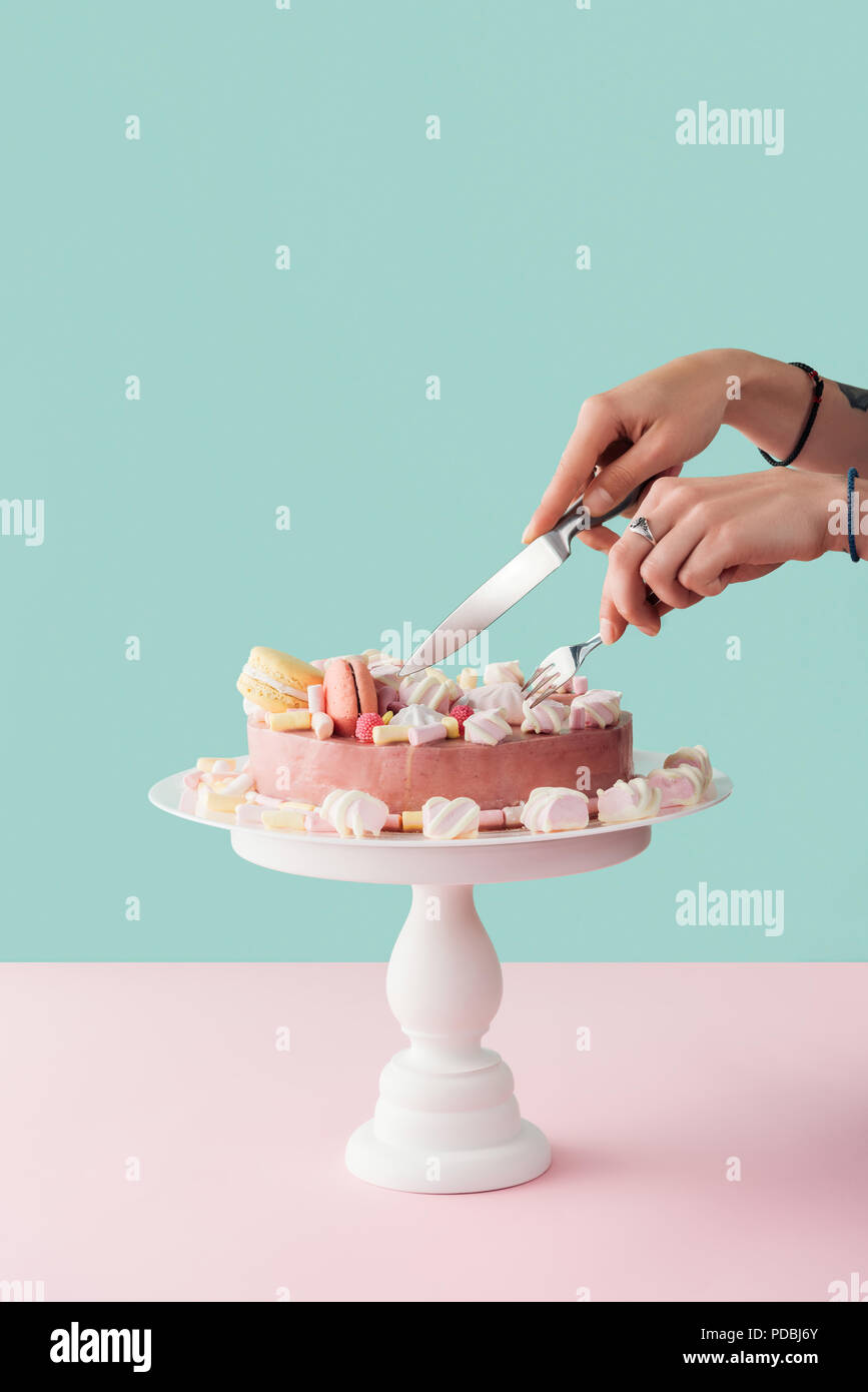 Cropped View Of Woman Cutting Marshmallow Cake With Knife And Fork