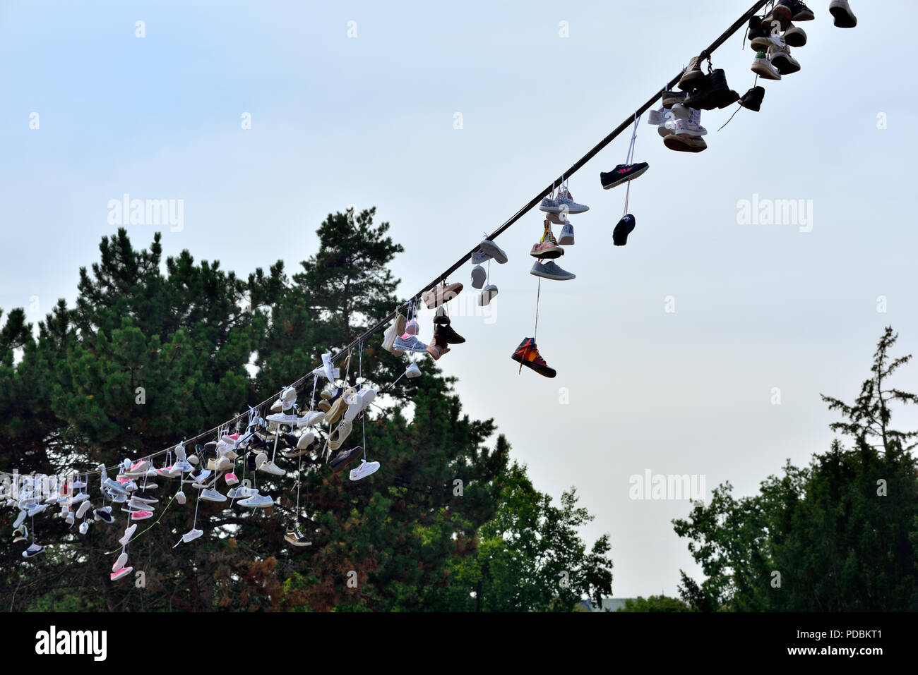 Shoes and boots hanging from an overhead wire at Prague Metronome, Czech Republic - Stock Image