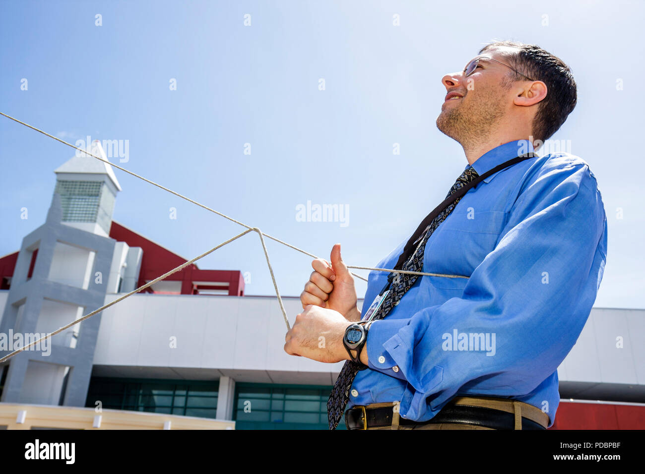 Miami Beach Florida Convention Center controls helium filled balloon man rope guide - Stock Image
