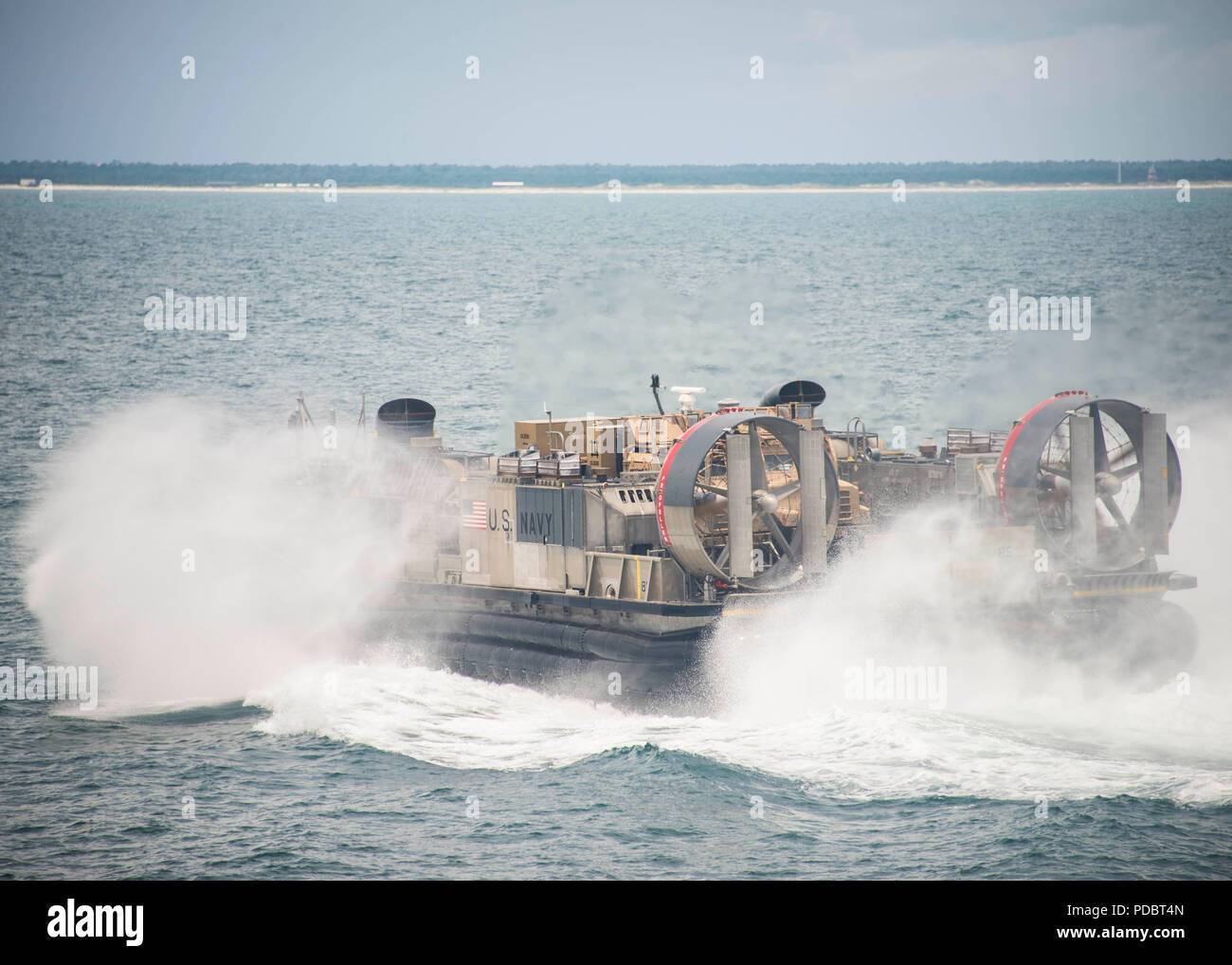 ATLANTIC OCEAN (Aug. 4, 2018) A landing craft, air cushion, attached to Assault Craft Unit 4, departs the Wasp-class amphibious assault ship USS Iwo Jima (LHD 7), Aug. 4, 2018. Iwo Jima is deployed with its amphibious ready group in support of maritime security operations and theatre security cooperation efforts in Europe and the Middle East. (U.S. Navy photo by Mass Communication Specialist 3rd Class Dominick A. Cremeans/Released) Stock Photo