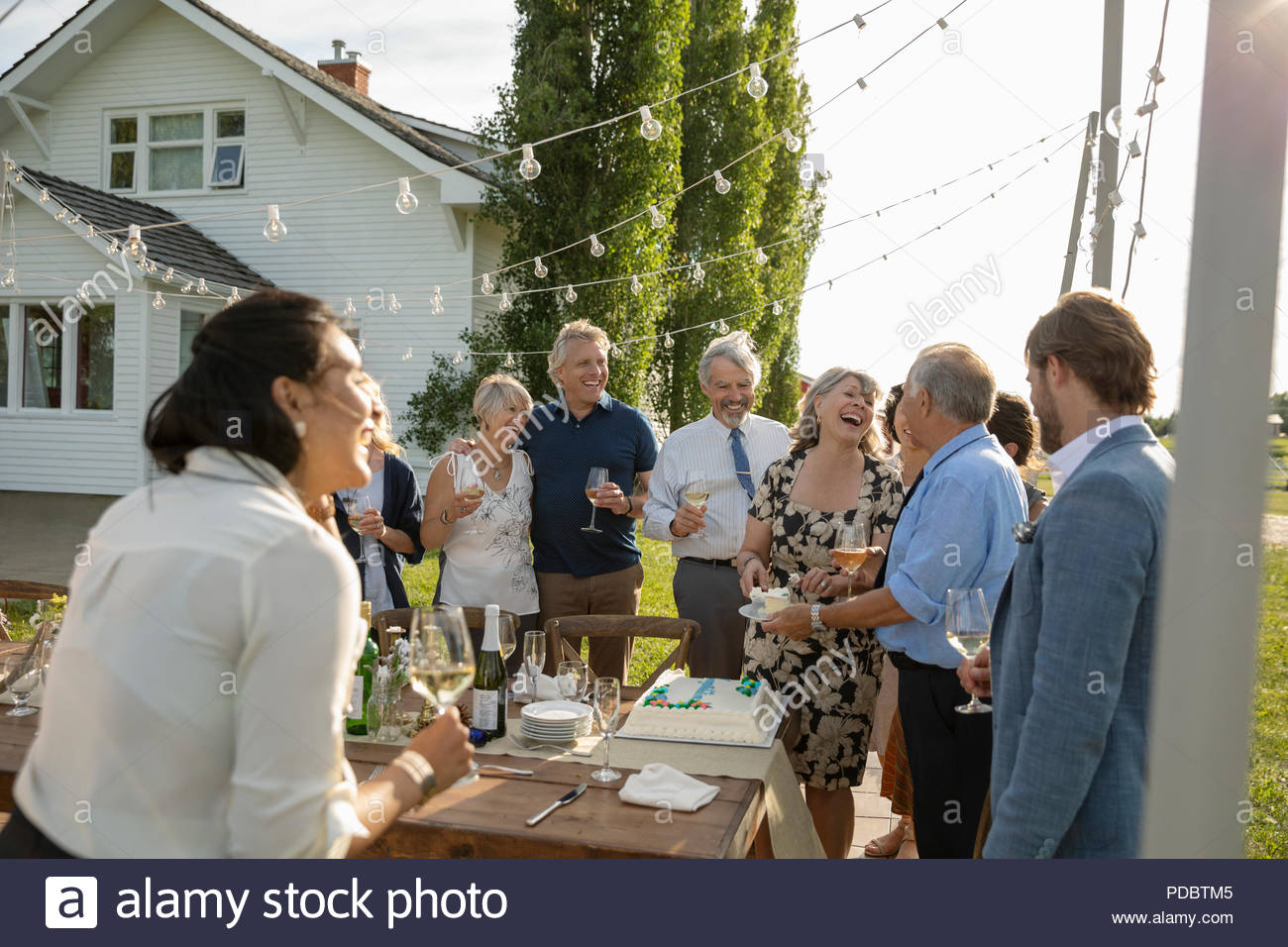 Friends celebrating, drinking wine and cutting cake at anniversary party at patio table - Stock Image