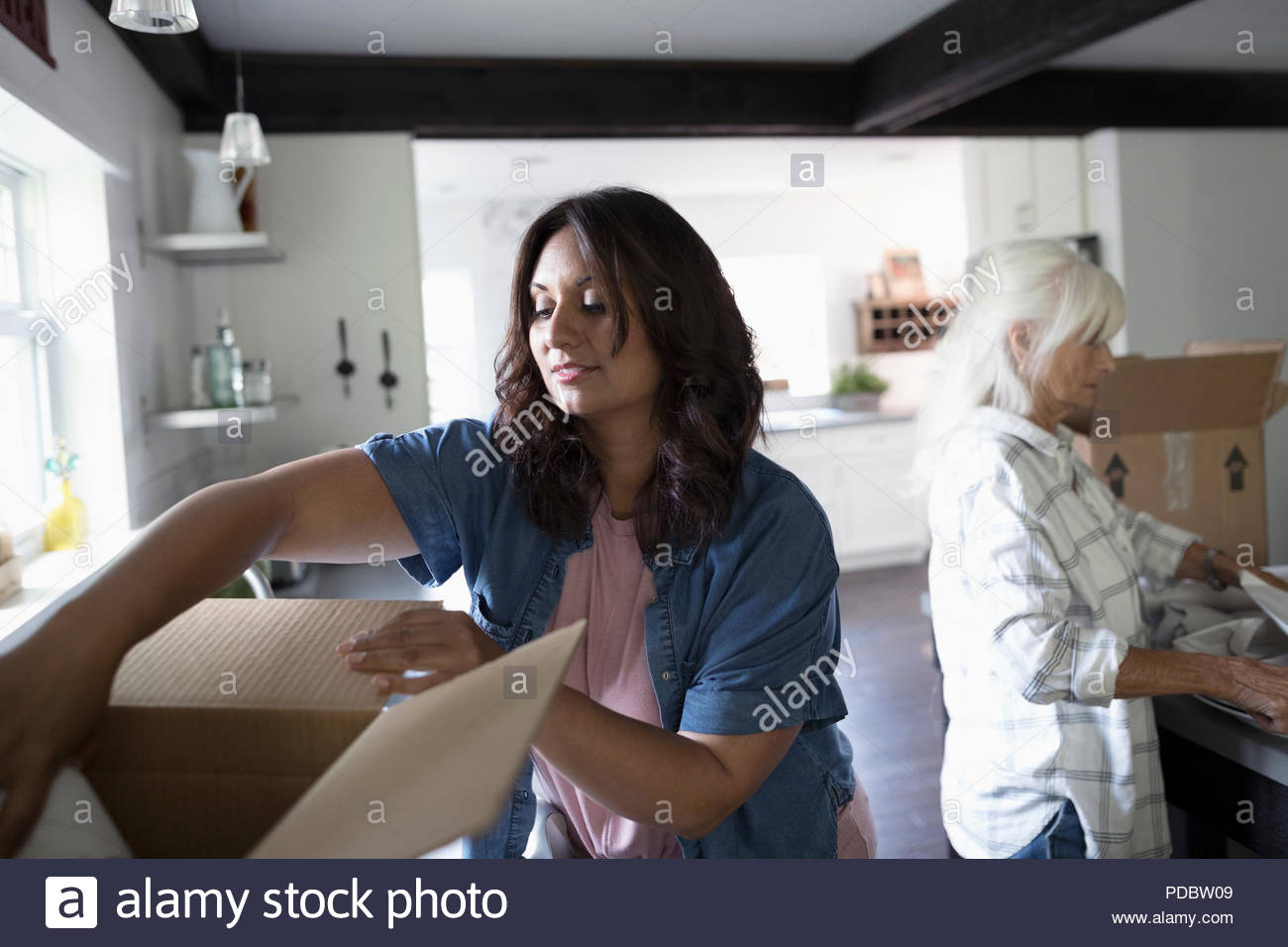Daughter helping senior mother downsize, packing kitchen Stock Photo