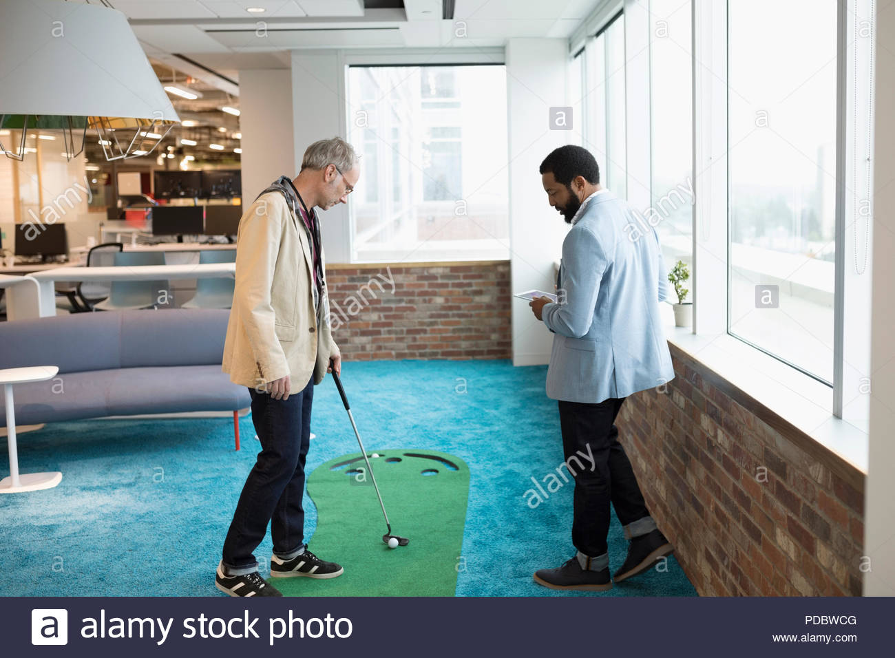 Creative businessman practicing putting in office - Stock Image