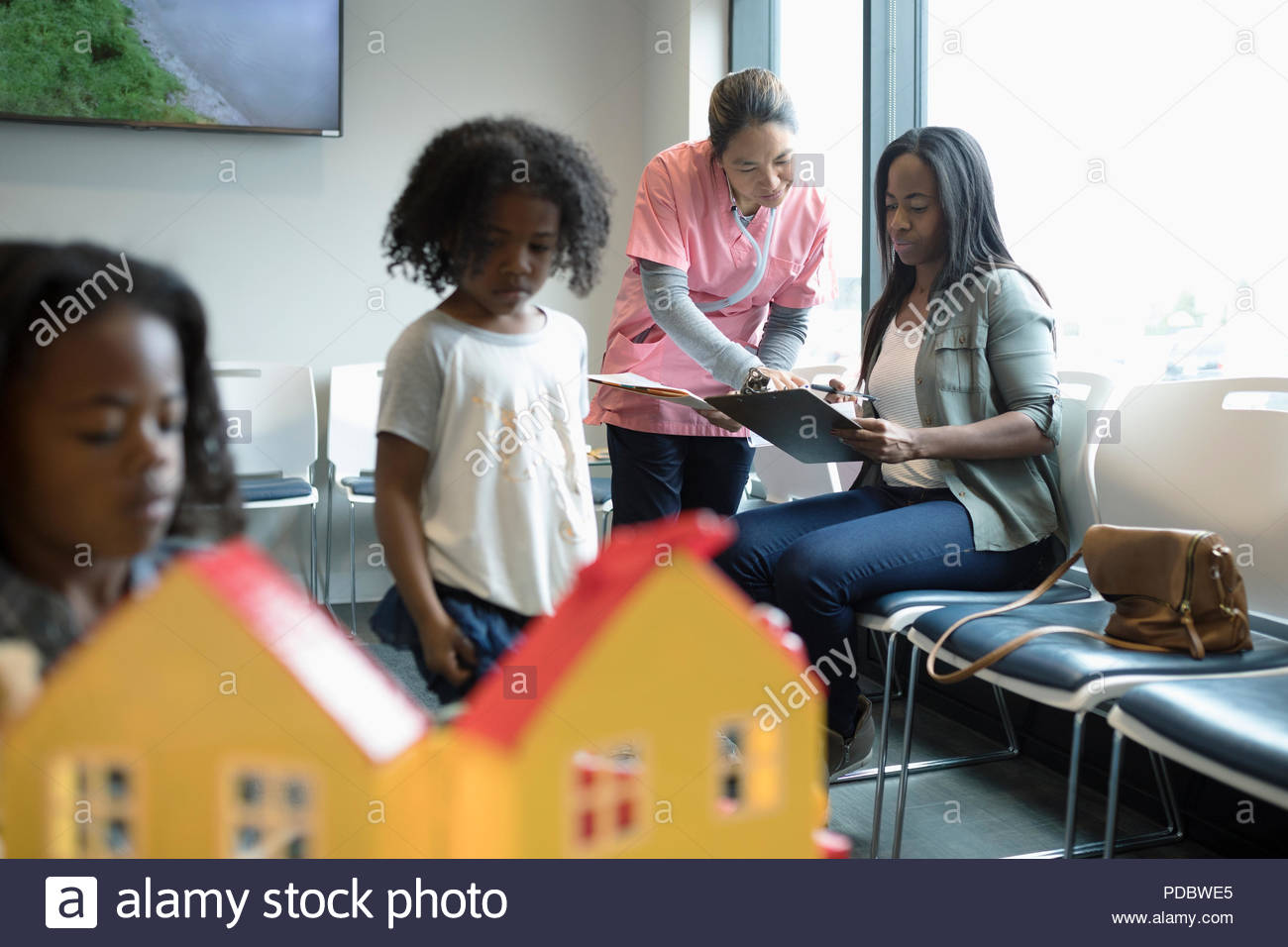 Nurse helping mother patient fill out paperwork in clinic waiting room - Stock Image