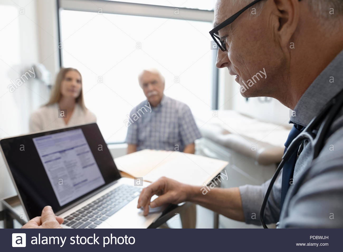 Male doctor using laptop with senior patient and daughter in background - Stock Image