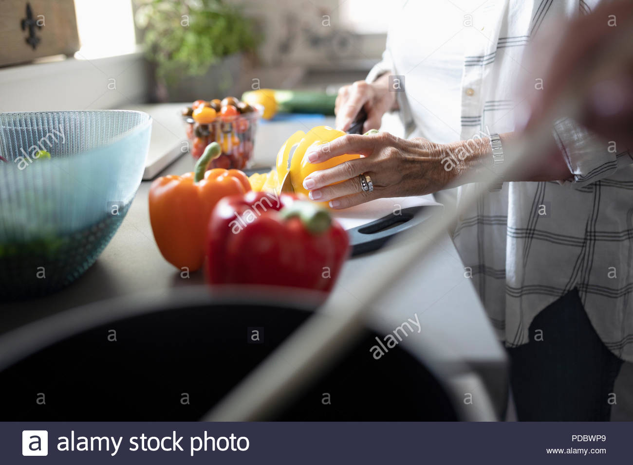 Close up senior woman cutting bell peppers, cooking in kitchen - Stock Image
