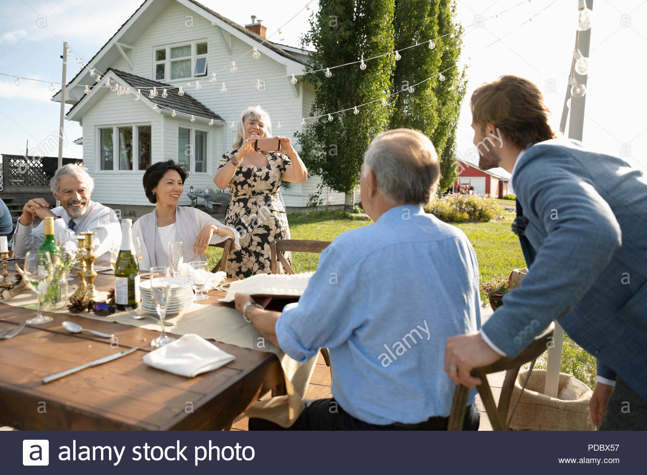 Woman photographing father and son at retirement party table - Stock Image