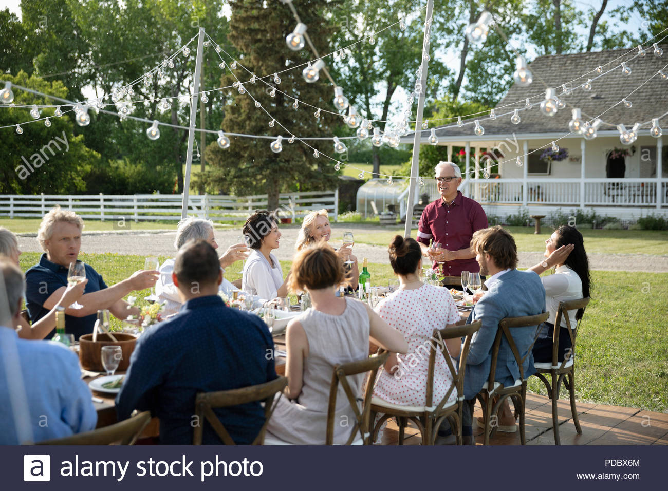 Senior man giving celebratory toast at garden party table - Stock Image