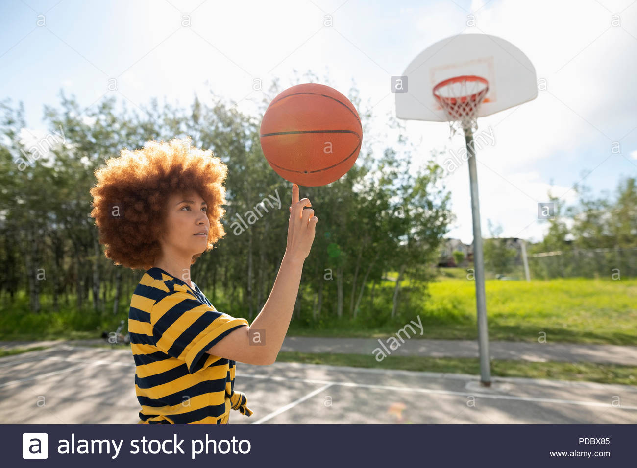 Cool teenage girl with afro balancing basketball on finger at park basketball court - Stock Image