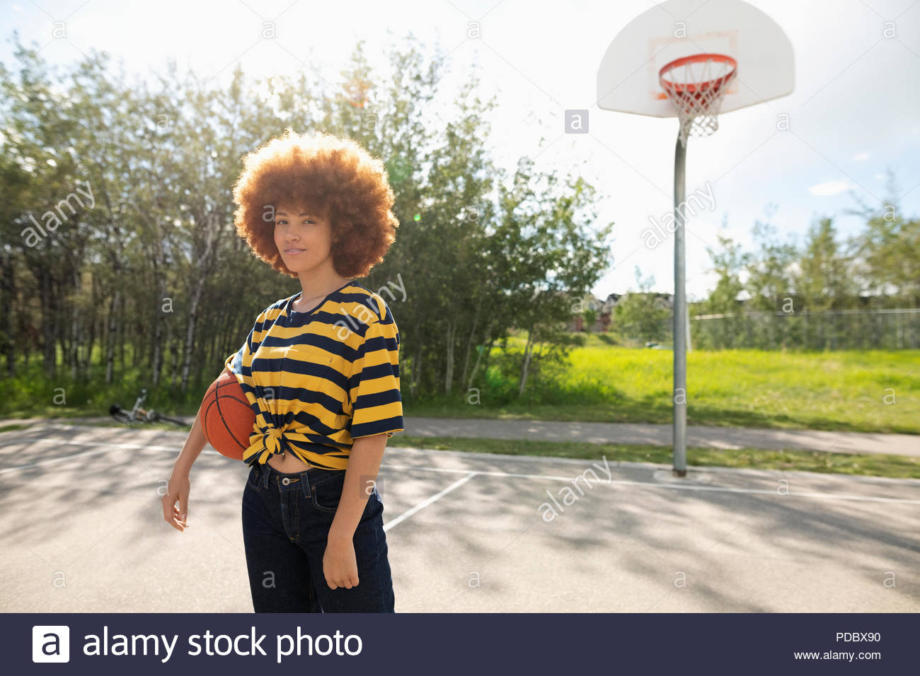 Portrait confident, cool teenage girl with afro playing basketball at park basketball court - Stock Image