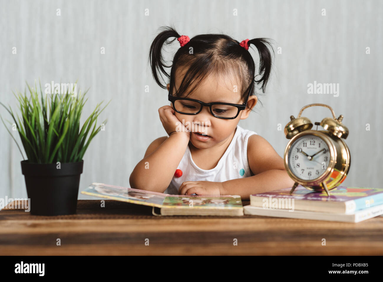 cute serious looking little asian toddler wearing spectacle reading