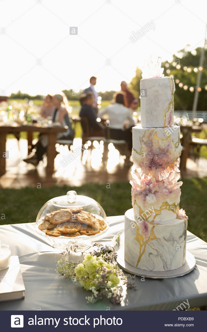 Tiered wedding cake and flowers on patio table - Stock Image