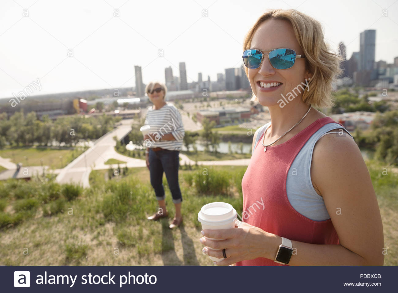 Portrait smiling woman drinking coffee and walking in sunny urban park with mother Stock Photo