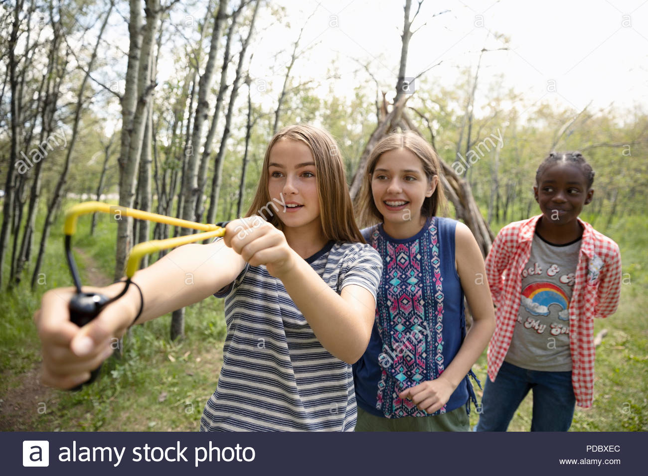 Playful tween girl friends playing with slingshot in woods Stock Photo