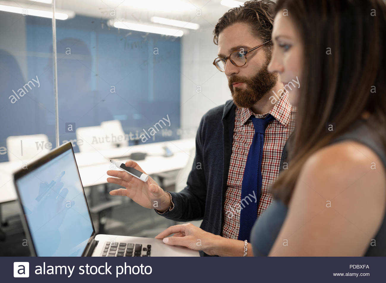 Business people with laptop planning, brainstorming in office - Stock Image