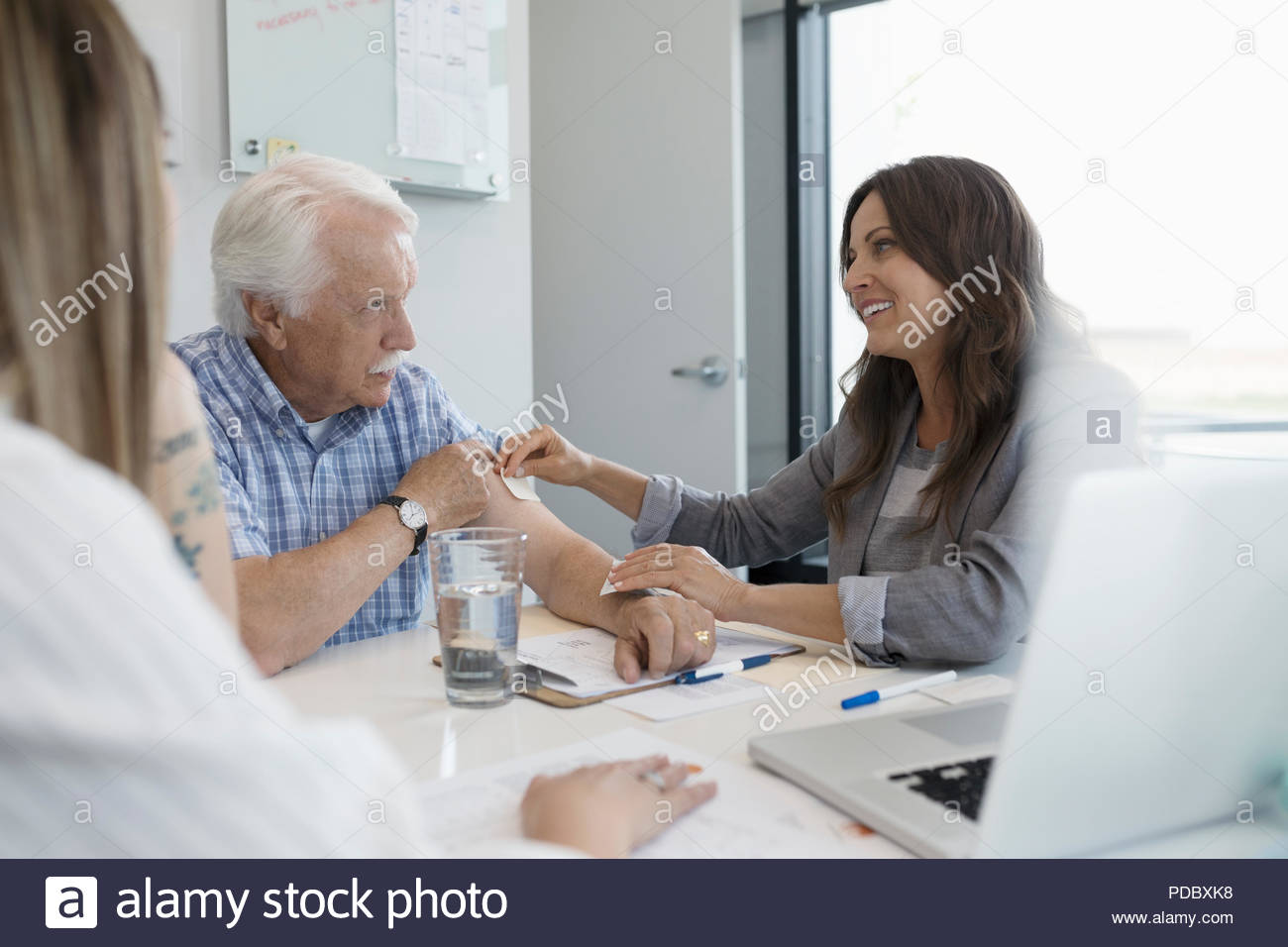 Female doctor applying smoking patch to arm of senior male patient in clinic office Stock Photo