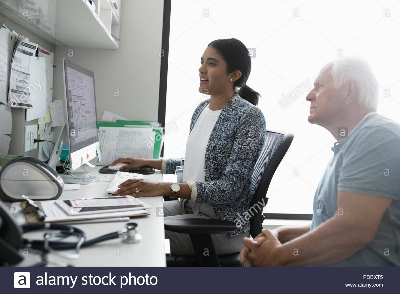 Female doctor and senior male patient at computer in clinic office - Stock Image