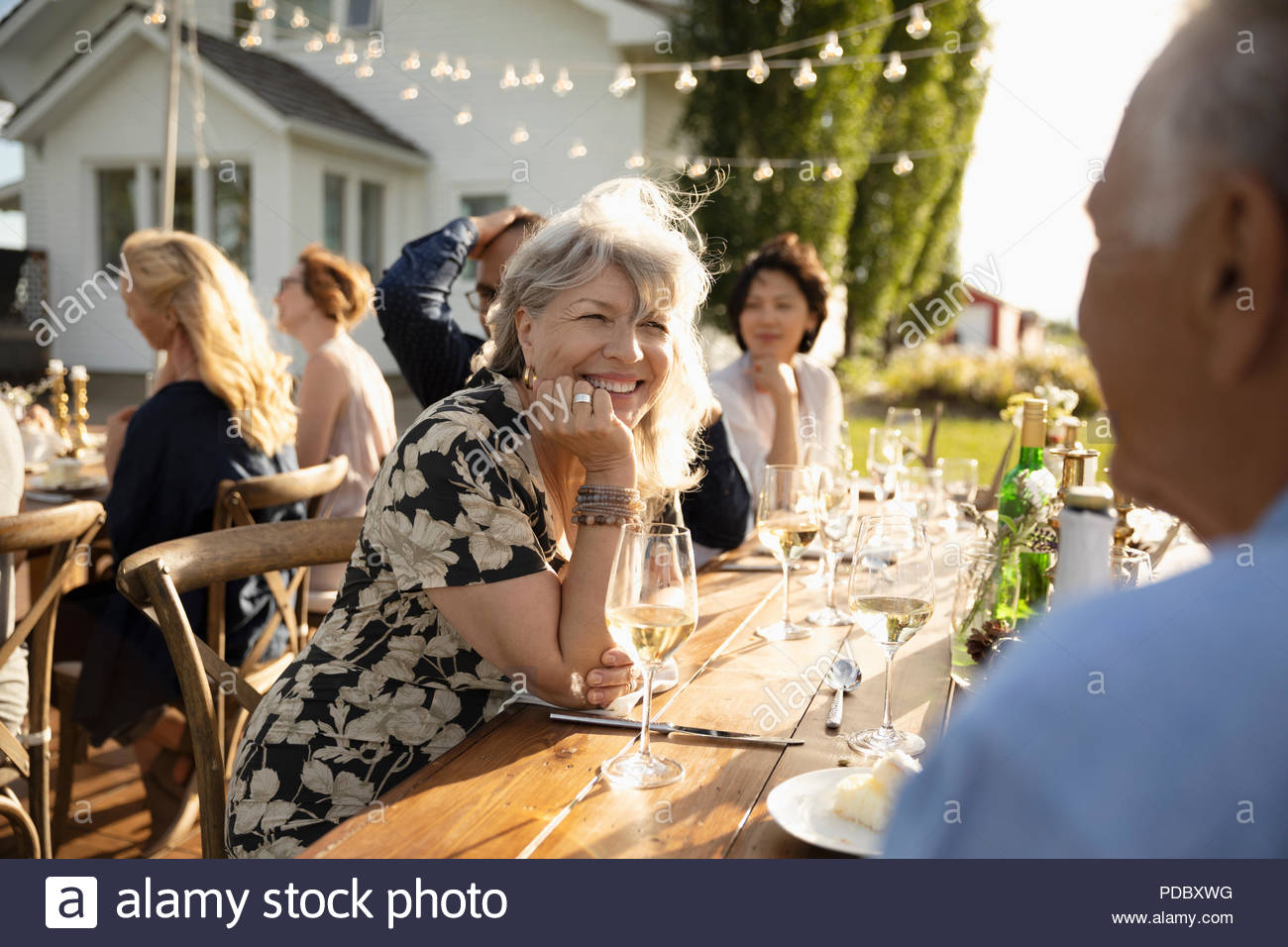 Smiling woman drinking wine, talking with man at sunny garden party - Stock Image