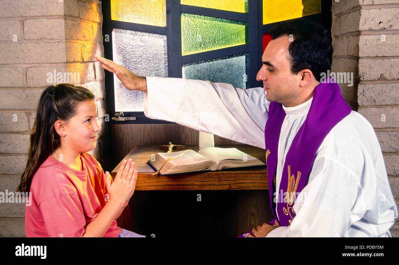 Catholic priest blessing child with hand held over Child's head during reconciliation.  © Myrleen Pearson  ....Ferguson Cate - Stock Image