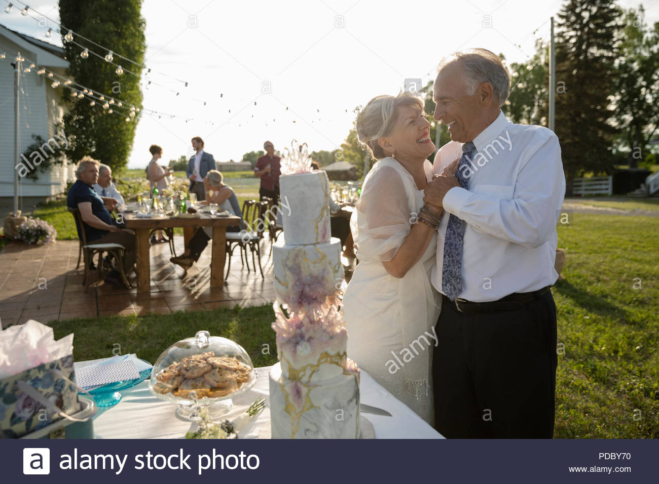 Affectionate senior bride and groom standing at wedding cake - Stock Image