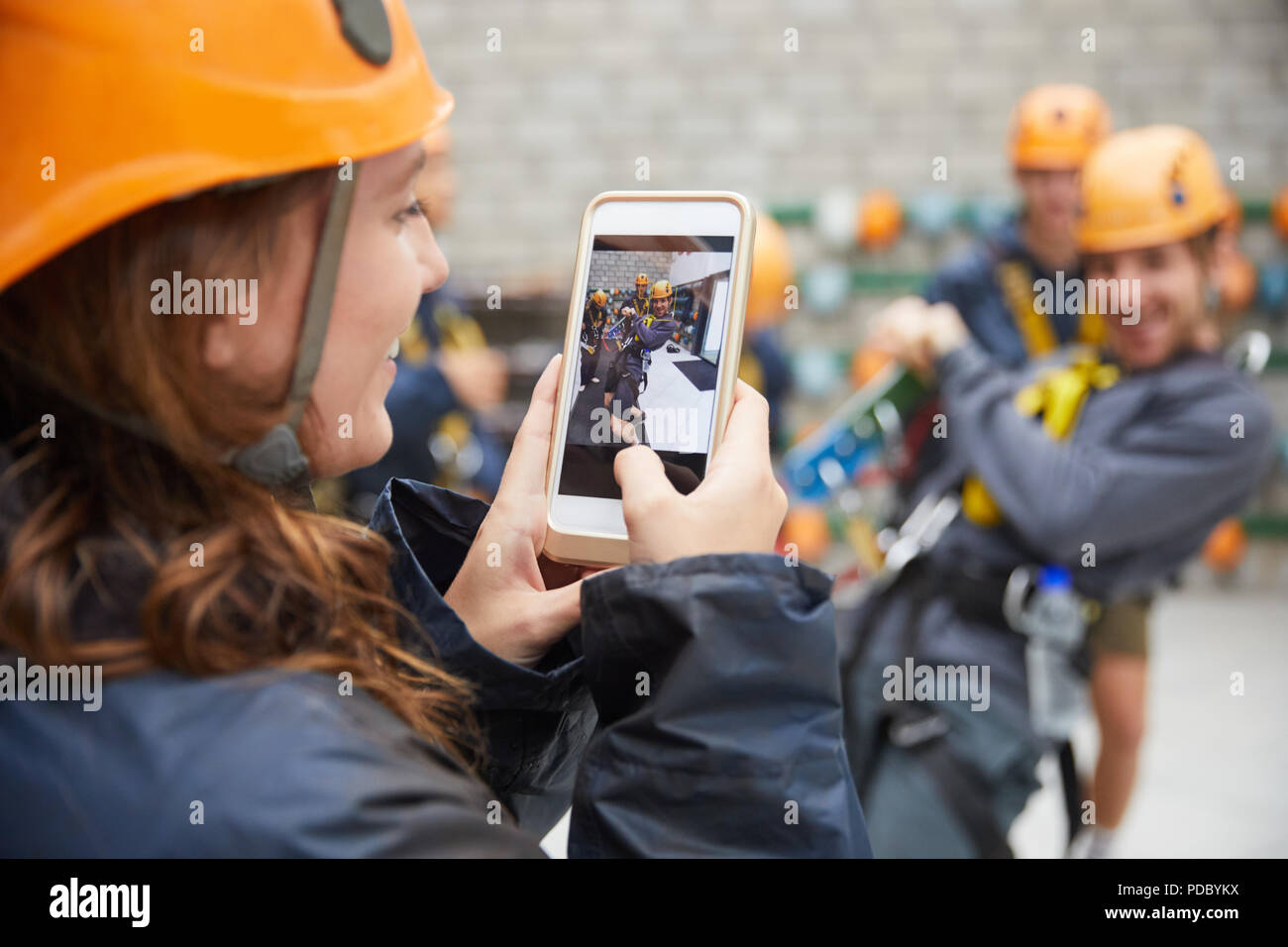 Woman with camera phone photographing friends in zip line equipment - Stock Image