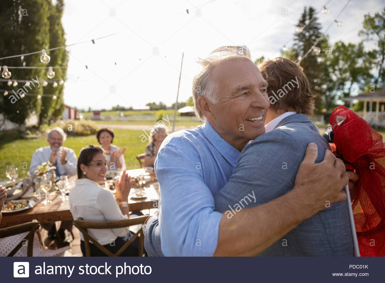 Grateful father hugging son at retirement party in rural garden with friends - Stock Image