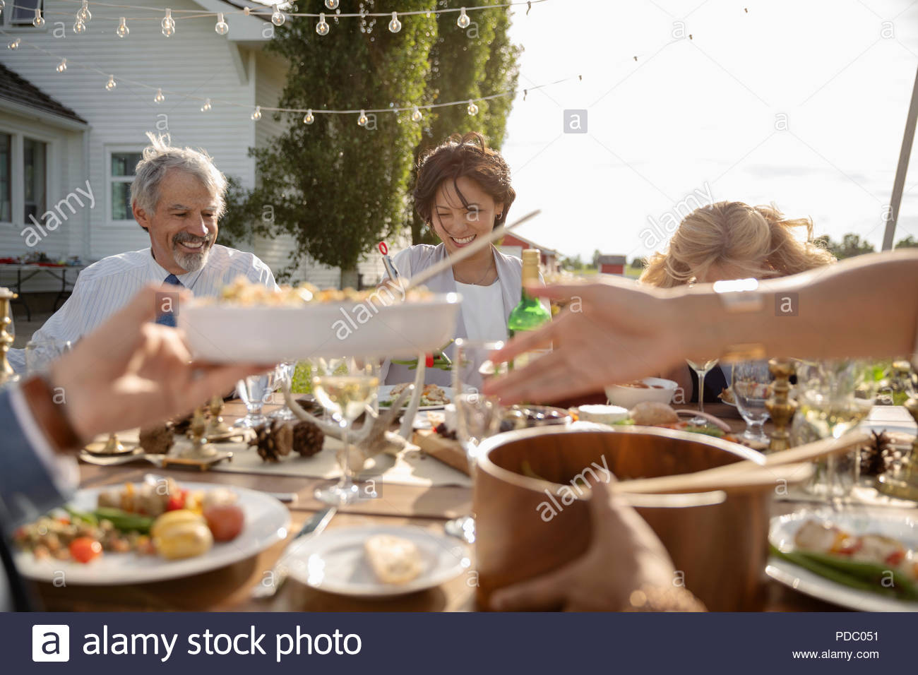 Friends eating and drinking at wedding reception at sunny rural table - Stock Image